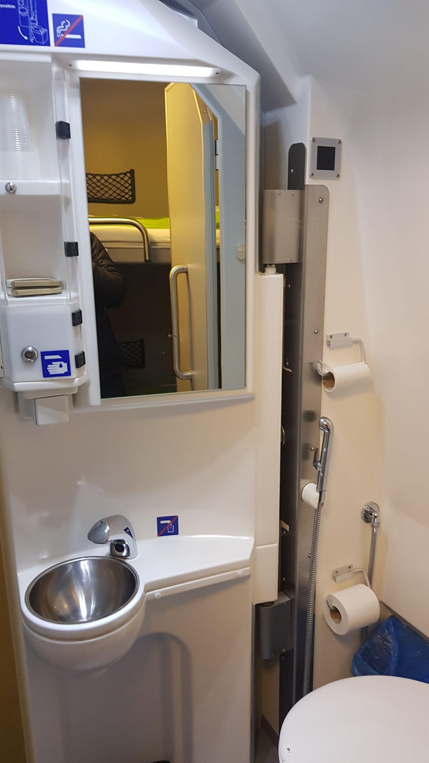 Cuarto de baño individual del tren santa claus express con su espejo,lavabo y váter.
