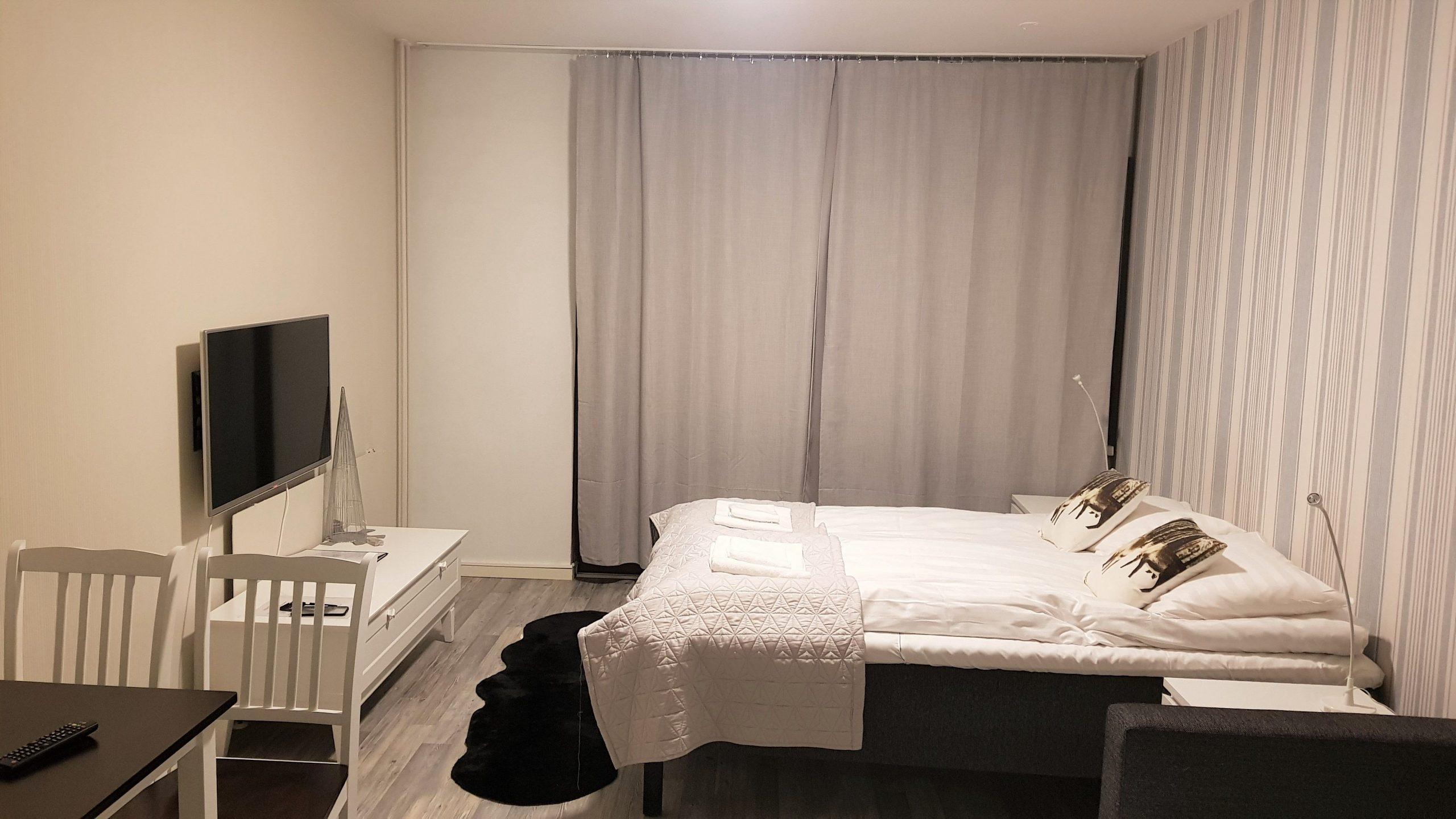 Habitación con cama de matrimonio y tele plana en Santa´s Holiday Homes.