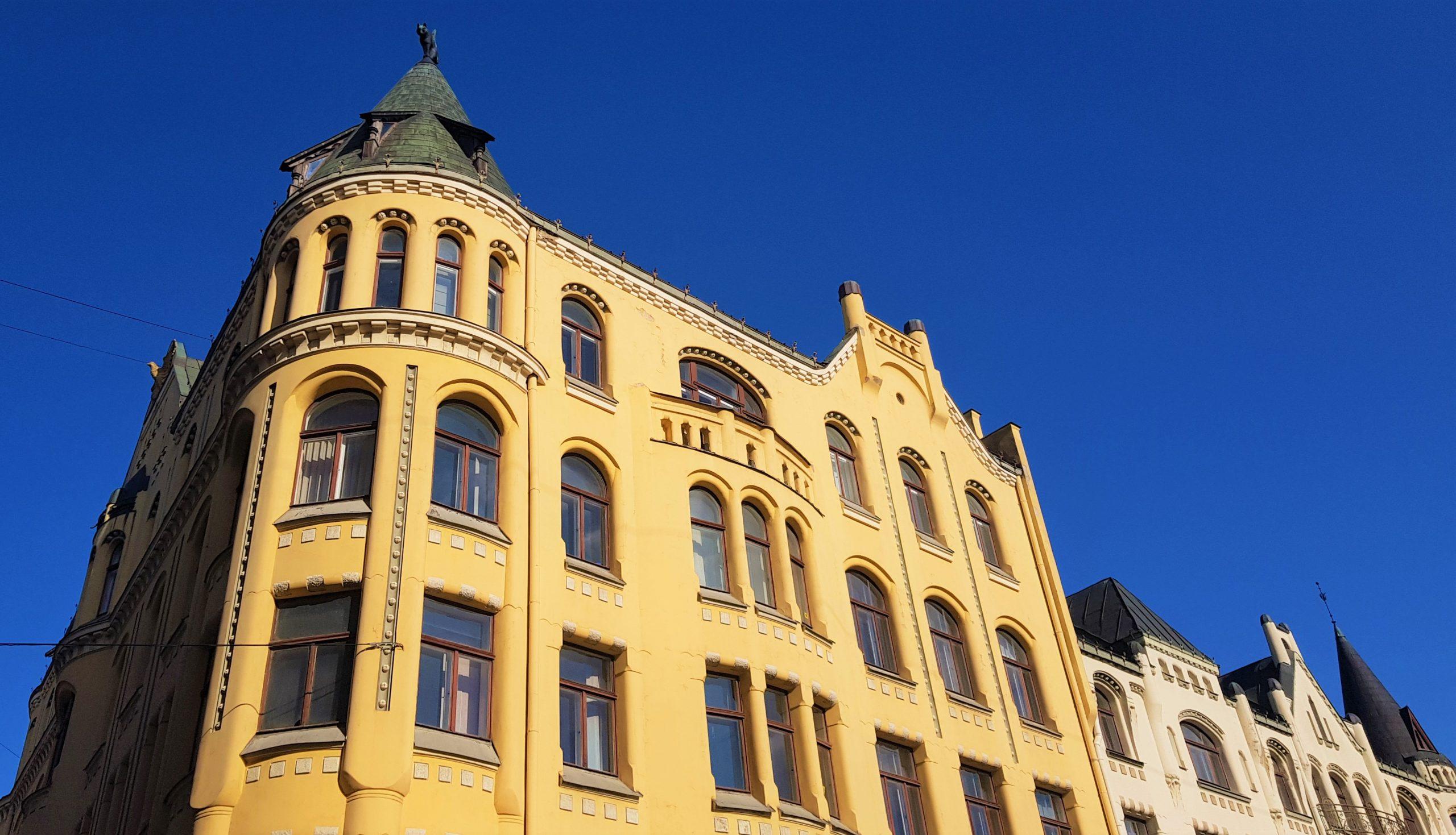 Edificio amarillo con varias esculturas de gatos coronando el tejado en Riga.