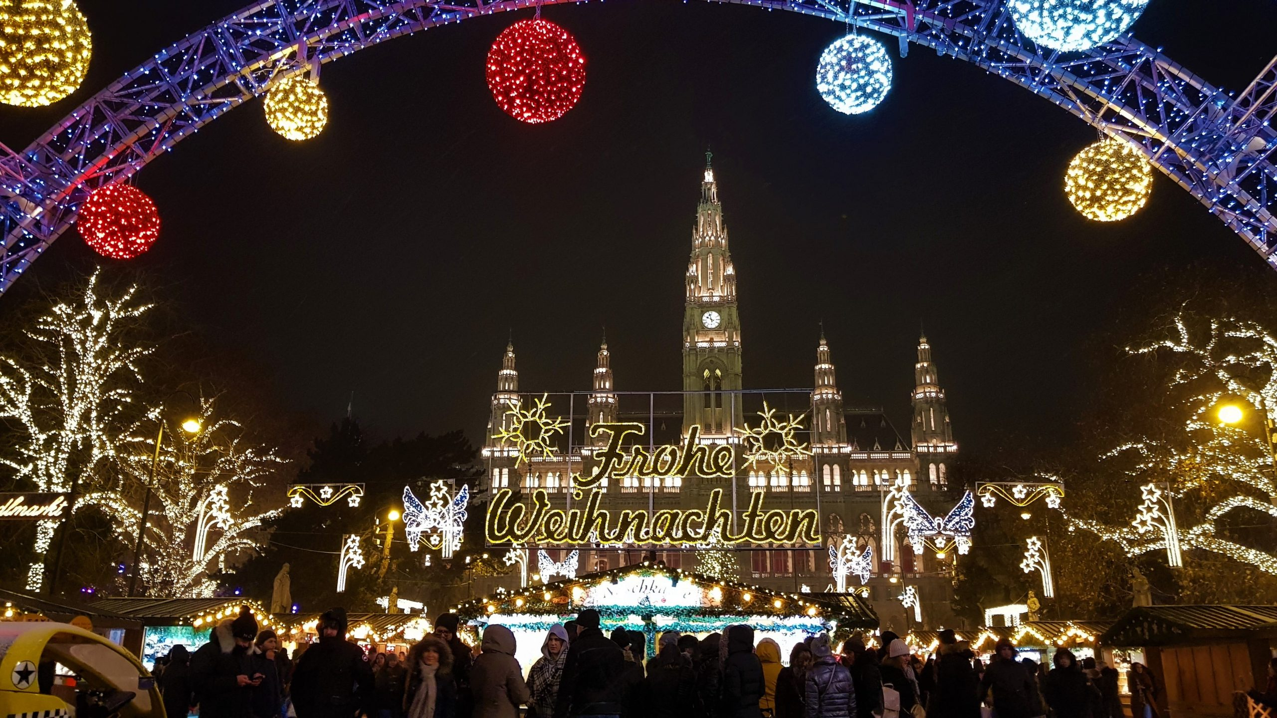 Mercado de Christkindlmarkt en Vienade de noche con el ayuntamiento de fondo